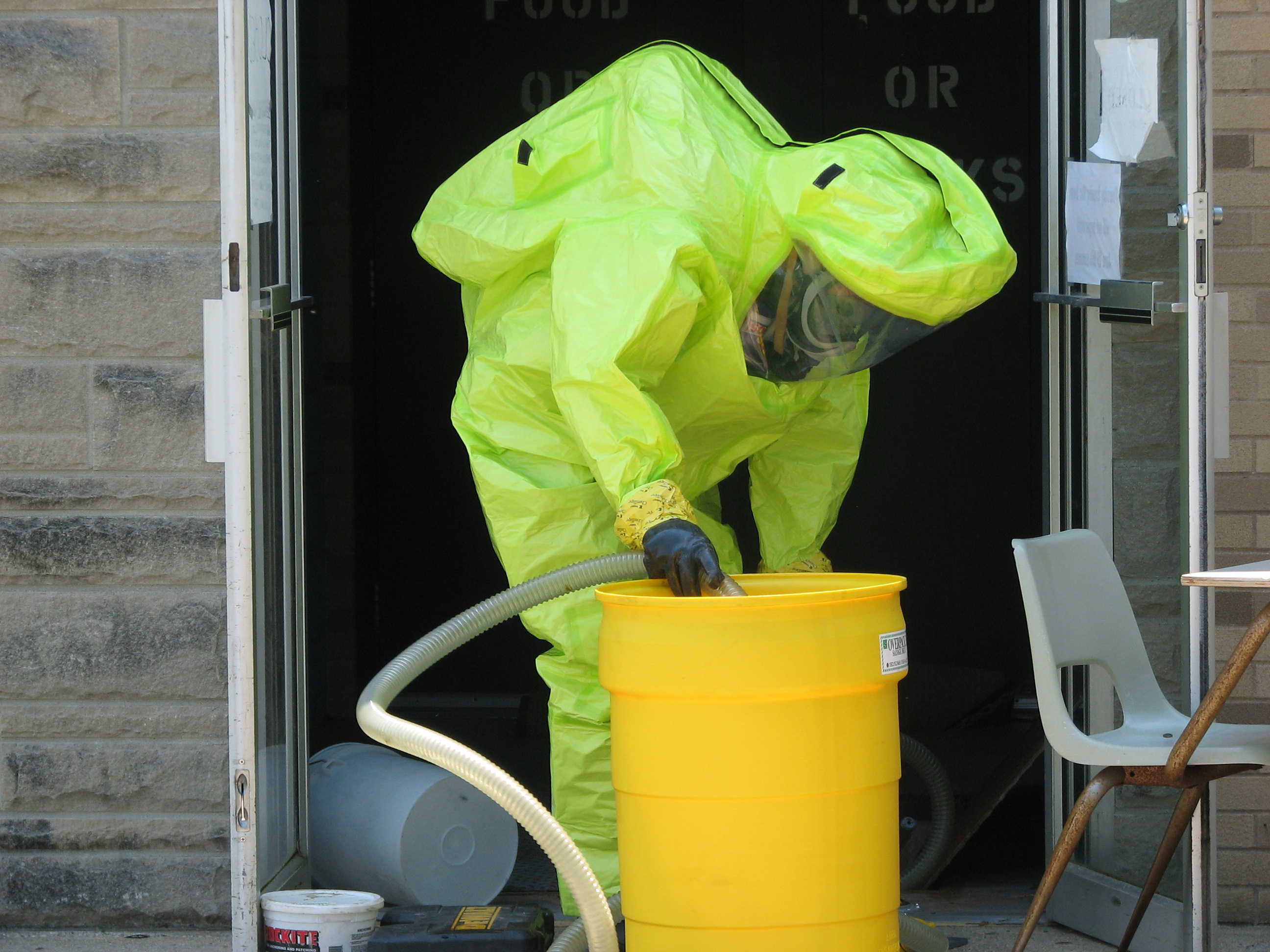 Carroll Incident - HazMat Team Member in HazMat Suit with a hose and a barrel